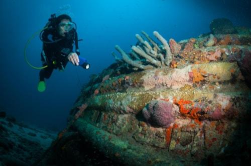 Woman diver examines a wreck on the Front Porch dive site, Bonaire, Netherlands Antilles