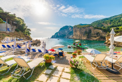 Sunbeds and umbrella on the beach in Corfu Island, Greece.