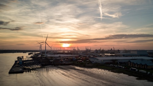 Sunset at the Port of Tilbury, Essex, UK. Aerial drone view of the port of Tilbury in Essex, England, with wind turbines and cranes dominating the skyline.