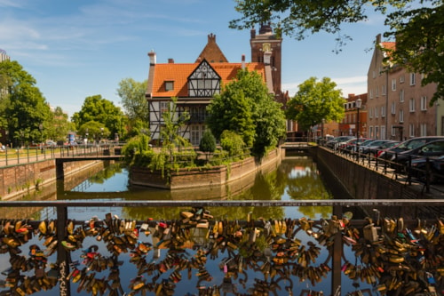 Scenic view on half-timbered building on the river island in european city, church tower on background and padlocks on bridge of love on foreground. Miller house, Grand Mill, Old Town, Gdansk, Poland